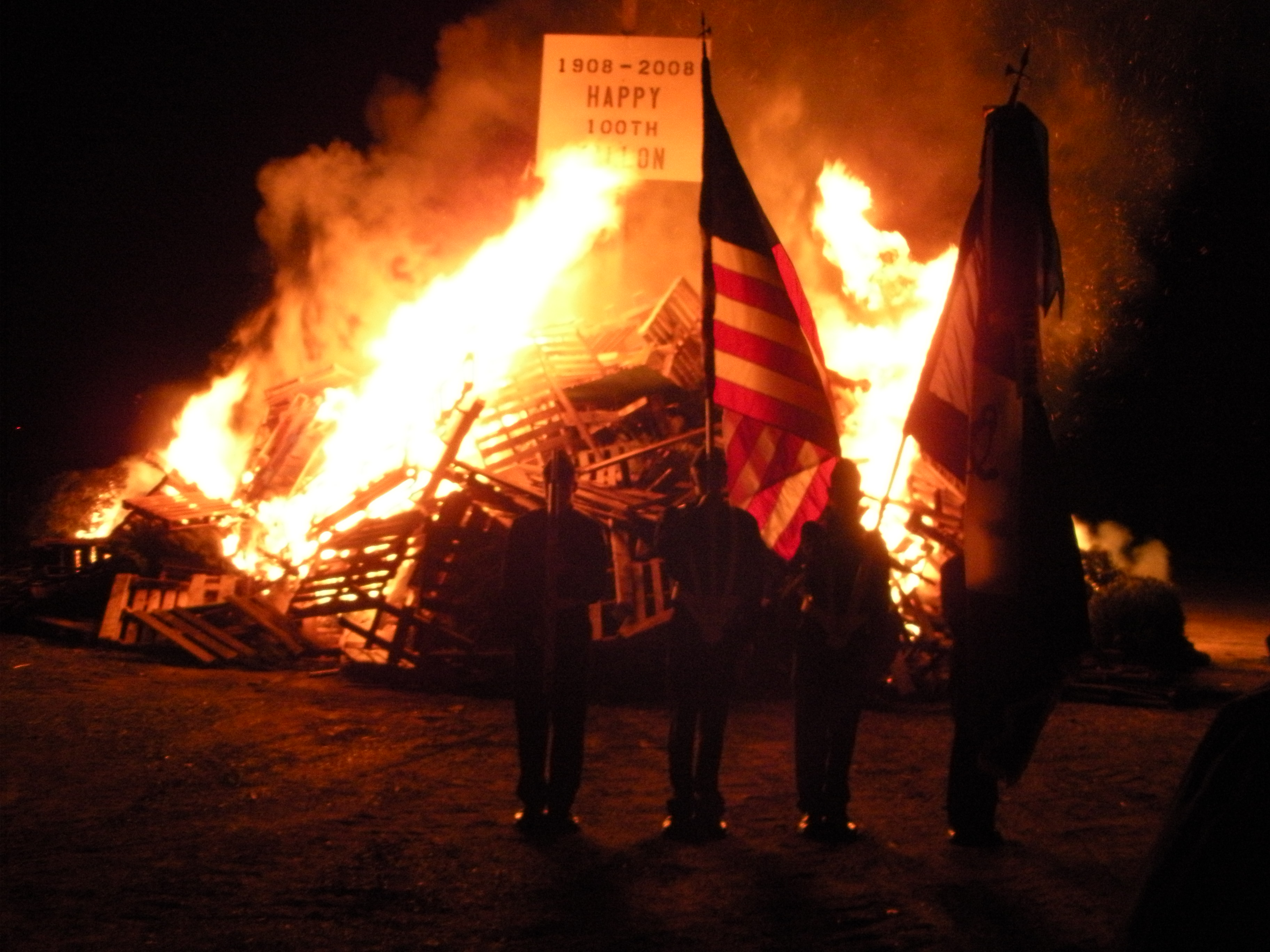 People Holding an American Flag Stand Before the Bonfire