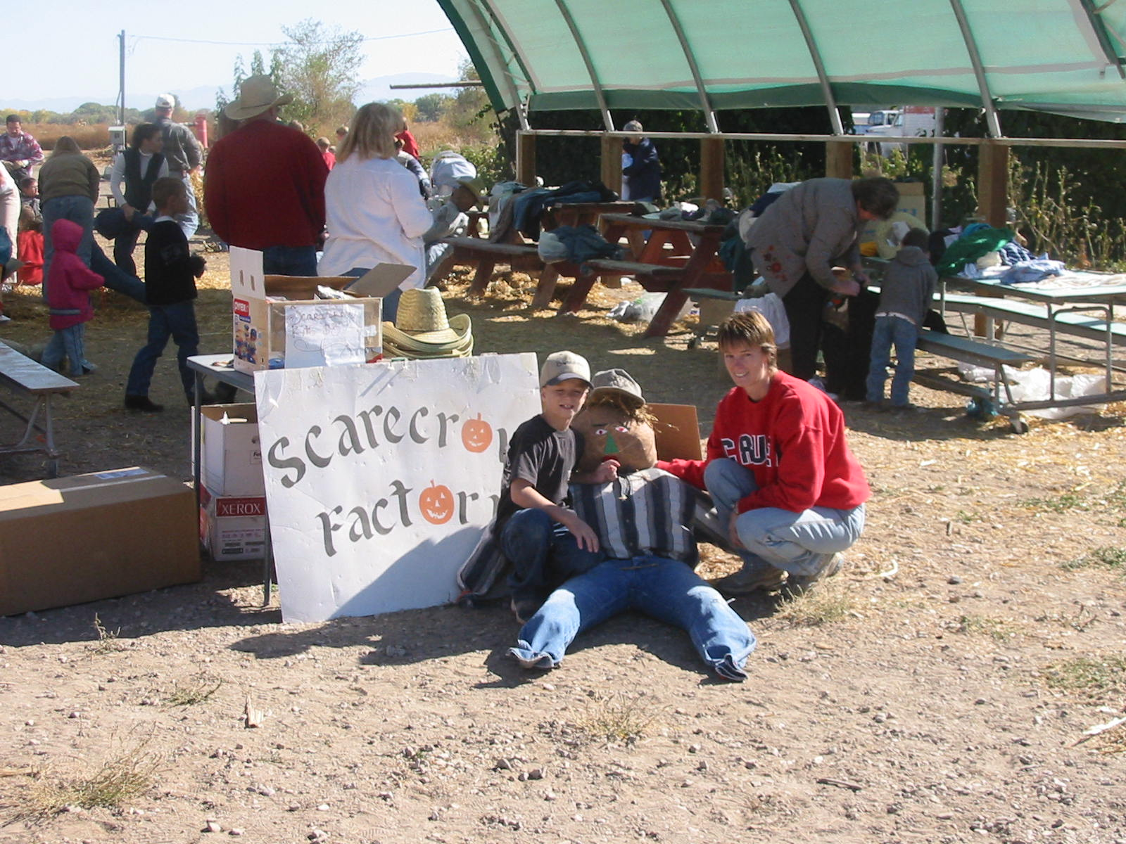 People Hold Their Scarecrow Next to Scarecrow Factory Sign