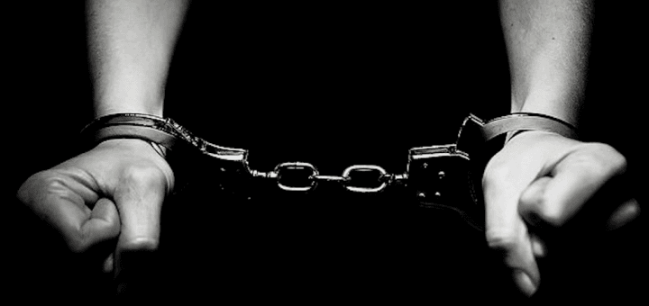 black and white picture of hands in handcuffs
