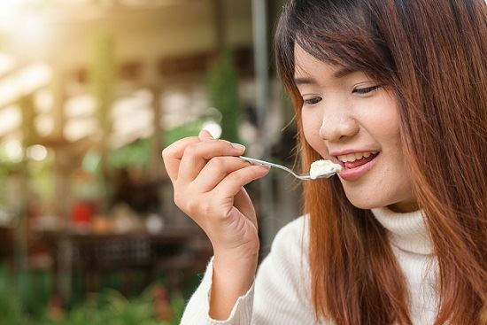 Woman holding spoon with food on it